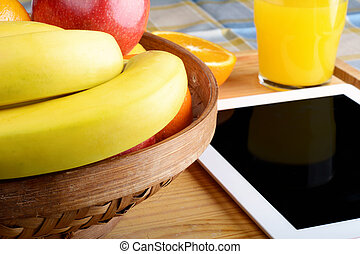 Fruits and a Tablet PC on wooden table.