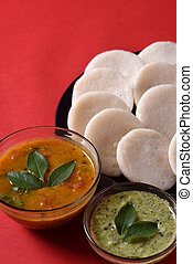 Idli with Sambar and coconut chutney on red background,...