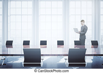 Man using laptop in conference room - Young businessman...