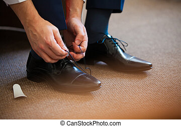 Man ties his shiney new black leather business shoes - Man...