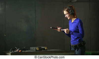 young woman with the gun on an indoor shooting range. collect gun