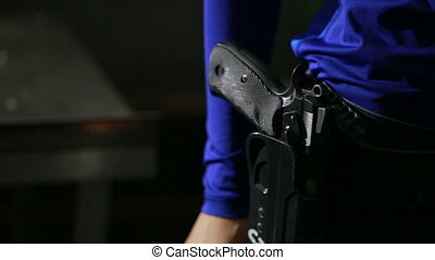 young woman with the gun on an indoor shooting range collect...
