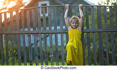 Little girl near the wood fence