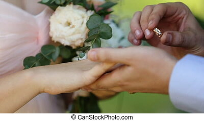 On a wedding outdoors ceremony groom puts a wedding ring on finger of a bride, close-up