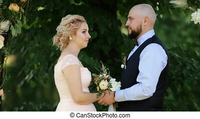 Wedding: beautiful young bride and groom standing in a park outdoors holding hands and smiling