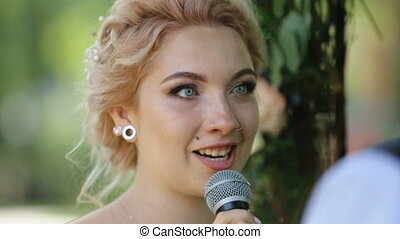 Beautiful blonde bride with nose ring taking vows at wedding...