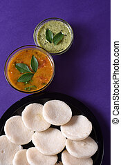 Idli with Sambar and coconut chutney on violet background,...