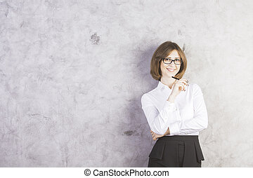 Smiling businesswoman against concrete wall - Attractive...