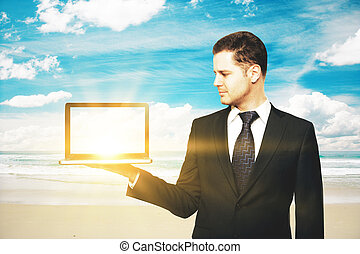 Man holding blank laptop at beach - Businessman holding...