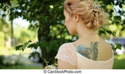 Smiling blonde bride with tattoo on her back and nose rang...