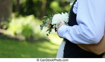 The bride standing behind groom and hugs him. Wedding session in the park