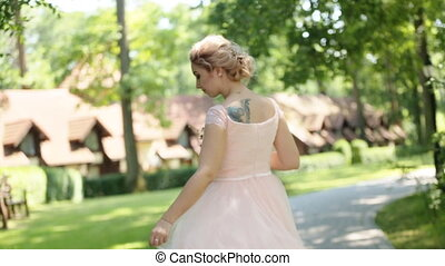 Close up of dreamy beautiful blonde bride with bouquet of roses dancing alone in the park and turning around