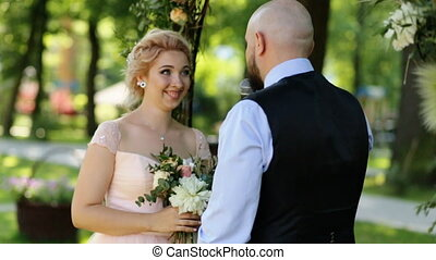 Handsome groom declaring at the outdoors wedding ceremony, while charming bride tenderly looking at him