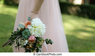 Beautiful wedding bouquet with white and pink roses in hands of bride walking outdoors