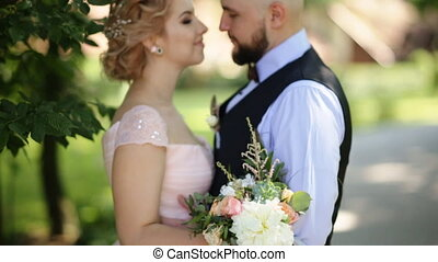 Handsome groom lovingly holds his beautiful bride while embracing her standing at sunny summer park