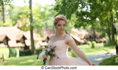 Beautiful romantic stylish blonde with owl tattoo in pink dress dancing in the park at the sunny day, close-up