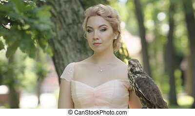 Mystery blonde woman holding a falcon on arm at foggy forest