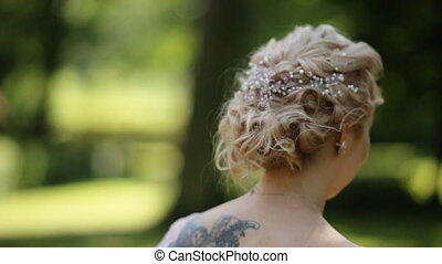 Beautiful blonde bride running in the green forest lit by...