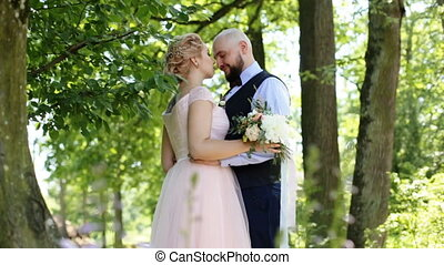 Close up of groom gently kissing his beautiful bride standing face-to-face in a hug, outdoors