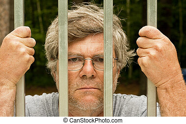 man behind bars - man in prison with hands wrapped around...