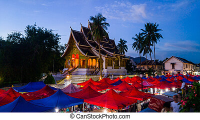 Night market in Luang Prabang, Laos with illuminated temple...