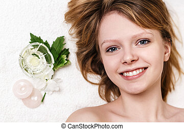 Atractive young girl relaxing in spa salon