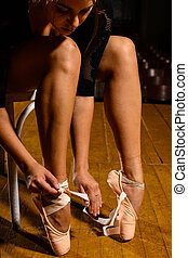 elegant ballet dancer tying her pointe shoes