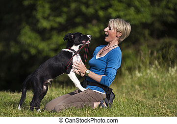 Woman with dog - Young woman playing with border collie dog...