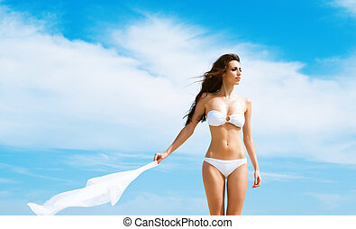 Young and sexy woman posing in a white swimsuit and holding...