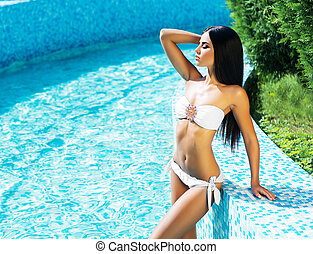 Seductive young woman in a swimsuit posing next to a pool -...