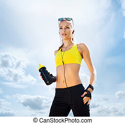 Young and fit woman in sporty clothes on a sky background -...