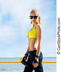 Young and fit woman in sporty clothes training outdoors -...