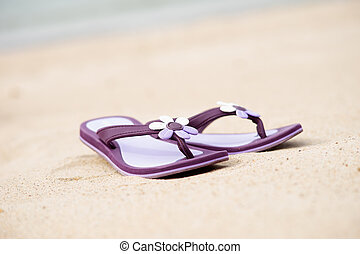 Beautiful purple flip-flops on the beach - Close-up of...