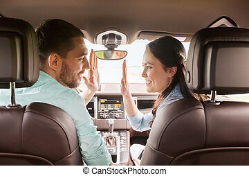 happy man and woman driving in car - leisure, road trip,...