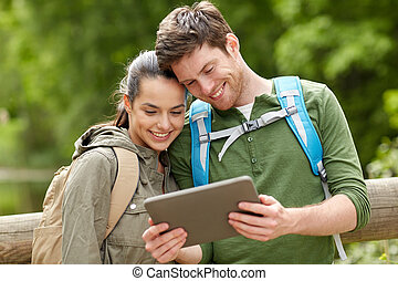 happy couple with backpacks and tablet pc outdoors - travel,...
