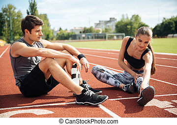 Athletic couple sitting and stretching legs together on...