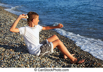 sitting boy throws stone in sea