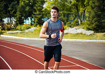 Young sports man running down stadium track with earphones -...
