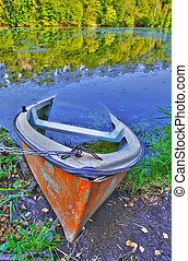Sinking boat ashore the pond - Old canoe ashore the pond is...