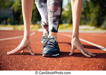 Cropped image of a female sprinter getting ready to run -...
