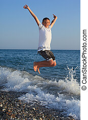 jumping teenager boy on stone seacoast
