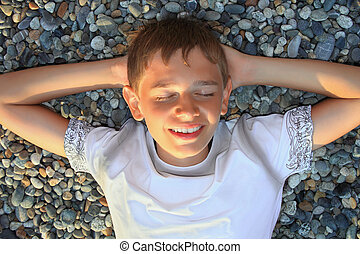 teenager boy lying on stones on stone seacoast, closed eyes,...