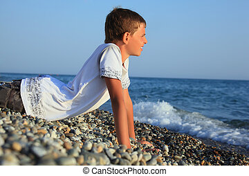 teenager boy lying on stones on seacoast