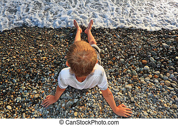 sitting teenager boy on stone seacoast, wets feet in water,...