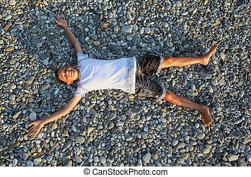 teenager boy lying on stones on stone seacoast