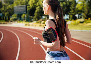 Side view of a female runner with mobile phone - Side view...