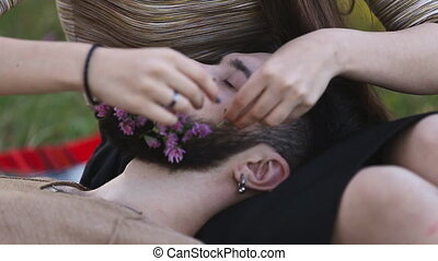 Girl puts a flower in his beard Man on nature