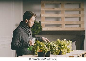 Handsome grower watering potted plants indoor.