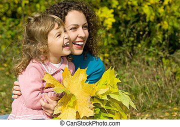 young woman and little girl laugh with leaves in hands in...
