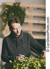 Handsome grower watering potted plants indoor
